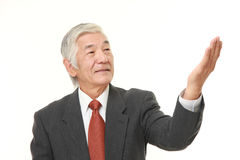 senior Japanese businessman presenting and showing something Royalty Free Stock Photography