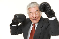 Senior Japanese businessman with punching glovesthrows in a victory pose Royalty Free Stock Photos
