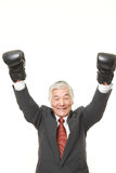 Senior Japanese businessman with punching glovesthrows in a victory pose Royalty Free Stock Photo