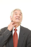 Senior Japanese businessman scratching his neck Royalty Free Stock Image