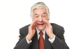 Senior Japanese businessman shout something. Studio shot of senior Japanese businessman on white background Stock Image