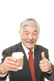 Senior Japanese businessman takes a coffee break. Studio shot of senior Japanese businessman on white background Stock Image
