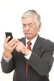 Senior Japanese businessman using smart phone looking confused Stock Photography