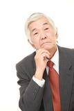 Senior Japanese businessman worries about something . Studio shot of senior Japanese businessman on white background Royalty Free Stock Photo
