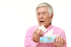 Senior Japanese man with an allergy sneezing into tissue  Stock Images
