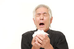 Senior Japanese man with an allergy sneezing into tissue Stock Photos