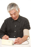 Senior Japanese man checking his blood pressure shocked Stock Image