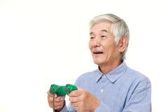 Senior Japanese man enjoying a video game Stock Photo