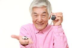 Senior Japanese man get a new car. Studio shot of senior Japanese man on white background Stock Photos