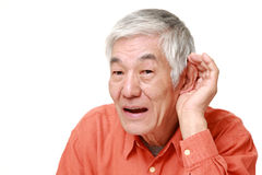 Senior Japanese man with hand behind ear listening closely Stock Photos