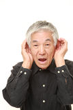 Senior Japanese man with hand behind ear listening closely Royalty Free Stock Photo