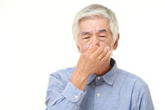 Senior Japanese man holding his nose because of a bad smell Royalty Free Stock Photos