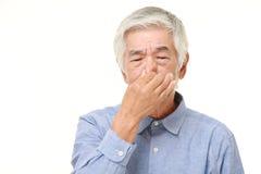 Senior Japanese man holding his nose because of a bad smell. Studio shot of senior Japanese man on white background royalty free stock photos