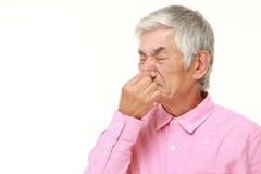 Senior Japanese man holding his nose because of a bad smell. Studio shot of senior Japanese man on white background royalty free stock image