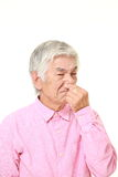 Senior Japanese man holding his nose because of a bad smell. Studio shot of senior Japanese man on white background royalty free stock photography