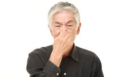 Senior Japanese man holding his nose because of a bad smell Stock Photos
