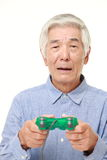 Senior Japanese man losing playing video game Stock Image