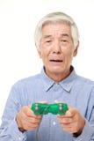 Senior Japanese man losing playing video game Stock Image