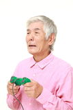 Senior Japanese man losing playing video game Stock Photo