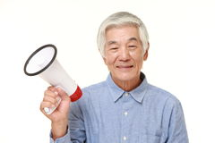 Senior Japanese man with megaphone. Studio shot of senior Japanese man on white background Stock Photography