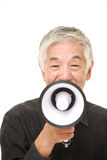 Senior Japanese man with megaphone. Studio shot of senior Japanese man on white background Royalty Free Stock Photos