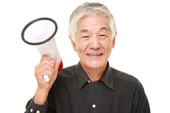Senior Japanese man with megaphone. Studio shot of senior Japanese man on white background Stock Photo