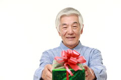 Senior Japanese man offering a gift Royalty Free Stock Photography