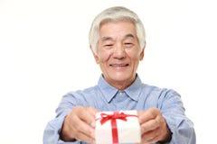 Senior Japanese man offering a gift Stock Photo