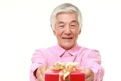 Senior Japanese man offering a gift Royalty Free Stock Image