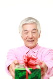 Senior Japanese man offering a gift Royalty Free Stock Photos