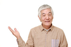 Senior Japanese man presenting and showing something Royalty Free Stock Image