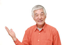 Senior Japanese man presenting and showing something. Portrait of senior Japanese man on white background royalty free stock photos