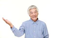 Senior Japanese man presenting and showing something. Studio shot of senior Japanese man on white background Royalty Free Stock Photos