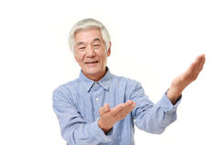 Senior Japanese man presenting and showing something Stock Photography