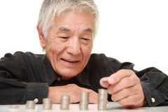 Senior Japanese man put coins to stack of coins Royalty Free Stock Photography