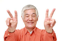 Senior Japanese man showing a victory sign Royalty Free Stock Photography