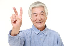 Senior Japanese man showing a victory sign Royalty Free Stock Image