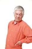 Senior Japanese man suffers from lumbago. Portrait of senior Japanese man on white background Stock Photography
