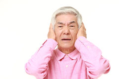 Senior Japanese man suffers from noise Royalty Free Stock Photography