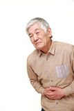 Senior Japanese man suffers from stomachache Stock Images