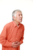 Senior Japanese man suffers from stomachache Royalty Free Stock Image