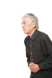 Senior Japanese man suffers from stomachache. Studio shot of senior Japanese man on white background Stock Photography