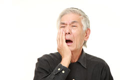 Senior Japanese man suffers from toothache Stock Photo