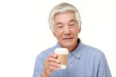 Senior Japanese man takes a coffee break Royalty Free Stock Image