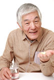 Senior Japanese man takes a supplement Stock Image