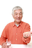 Senior Japanese man takes a supplement Stock Photo