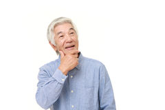 Senior Japanese man thinks about something. Studio shot of senior Japanese man on white background Stock Photos