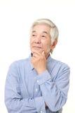 Senior Japanese man thinks about something. Studio shot of senior Japanese man on white background Royalty Free Stock Photos
