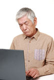 Senior Japanese man using computer looking confused Royalty Free Stock Photo