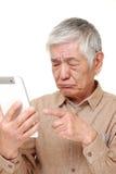 Senior Japanese man using tablet computer looking confused. Portrait of senior Japanese man using tablet computer looking confused on white background Stock Photo